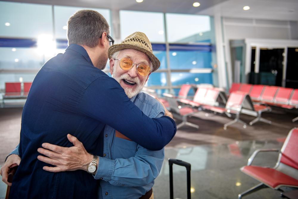 Elderly Muslim father hugging son